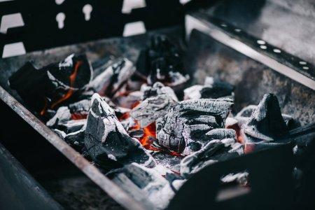 Foto de Selective focus of hot burning coals with ash in iron bbq grill - Imagen libre de derechos