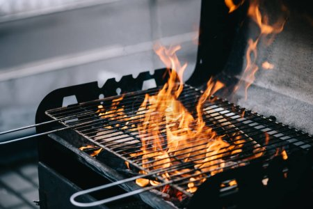 Photo for Burning firewood with flame through bbq grill grates - Royalty Free Image