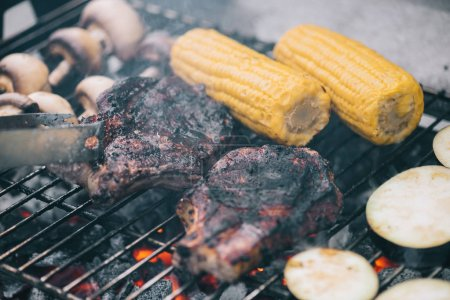 Photo for Selective focus of tweezers and juicy tasty steaks grilling on bbq grid with mushrooms, corn and sliced eggplant - Royalty Free Image