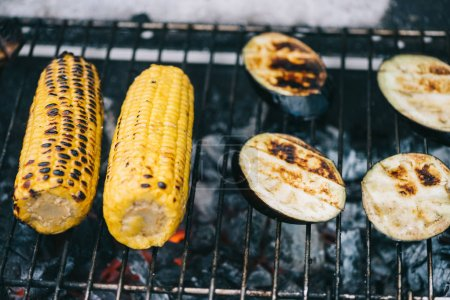 Photo for Selective focus of yellow corn with crust and eggplant slices grilling on barbecue grid - Royalty Free Image