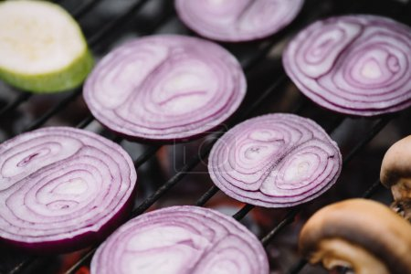 Photo for Selective focus of raw onion slices, zucchini and mushrooms grilling on barbecue grid - Royalty Free Image