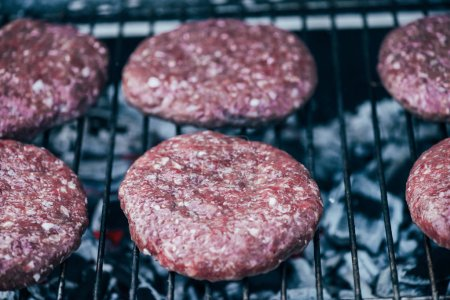 Photo for Close up of uncooked fresh burger cutlets grilling on bbq grid - Royalty Free Image