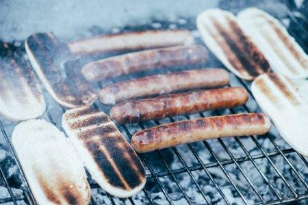 Photo pour Délicieux hot-dogs griller avec de la fumée sur le barbecue grill grade - image libre de droit