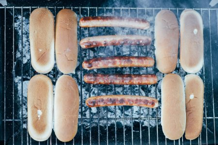 Photo for Top view of tasty hot dogs grilling with smoke on bbq grill grade - Royalty Free Image