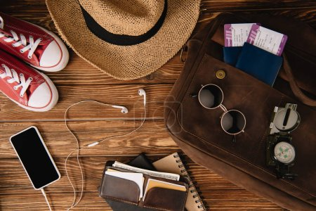 Photo for Top view of smartphone with earphones, passports with tickets and accessories with keds on wooden surface - Royalty Free Image