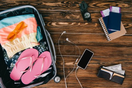 Photo for Top view of smartphone with earphones, compass, passports with tickets and summer clothes in travel bag on wooden surface - Royalty Free Image