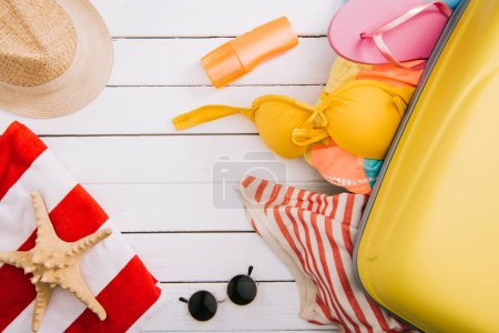 Photo for Top view of sunscreen, starfish and summertime accessories and clothes in suitcase on white wooden background - Royalty Free Image