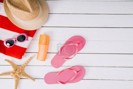 top view of sunscreen, starfish and summer accessories on white wooden background