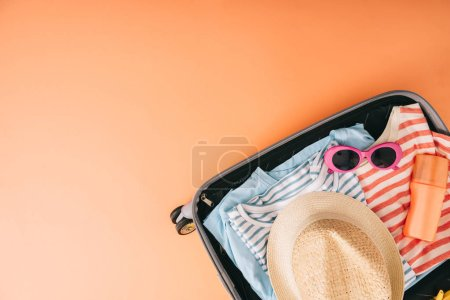 Photo for Top view of suitcase with summer accessories and sunscreen on orange background - Royalty Free Image