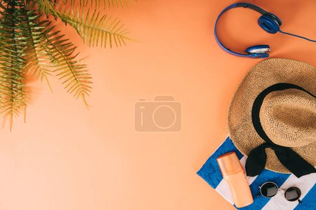 Photo for Top view of summer accessories, headphones and sunscreen on orange background with palm leaves - Royalty Free Image