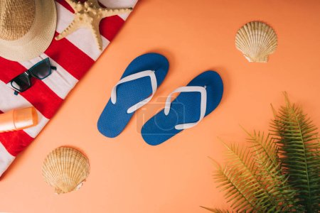 Photo for Top view of summer accessories and sunscreen on orange background with palm leaves and seashells - Royalty Free Image
