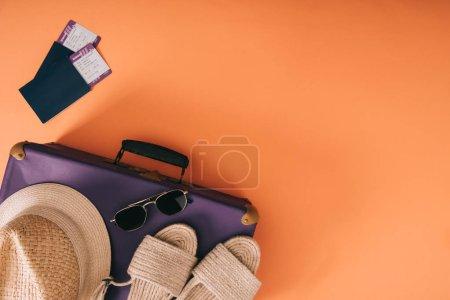 Foto de Vista superior de accesorios de verano en la bolsa de viaje con pasaporte y pasajes en fondo naranja - Imagen libre de derechos