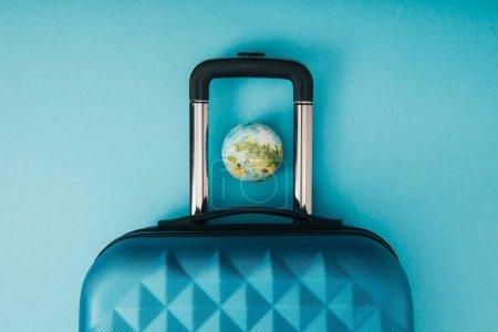 Foto de Vista superior del modelo de globo y la bolsa de viaje sobre fondo azul - Imagen libre de derechos