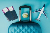 top view of globe and plane models, travel bag and passports with tickets on blue background