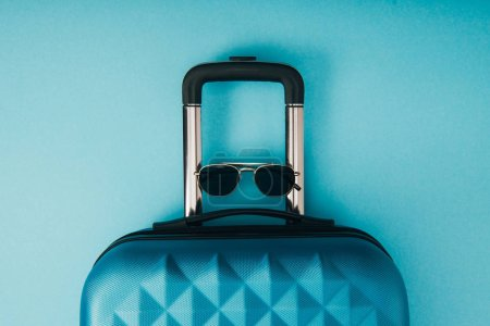 Photo for Top view of sunglasses and travel bag on blue background - Royalty Free Image