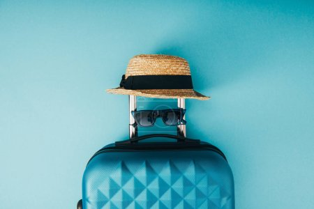 Photo for Top view of straw hat, sunglasses and travel bag on blue background - Royalty Free Image