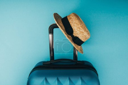 Photo for Top view of straw hat and travel bag on blue background - Royalty Free Image