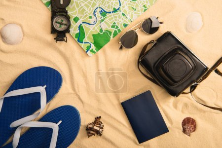 top view of summer accessories and map with compass on sand with seashells