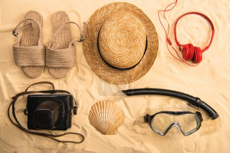 Photo for Top view of summer accessories, swimming mask with snorkel, headphones and film camera on sand - Royalty Free Image