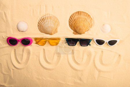 Photo for Top view of sunglasses and seashells with smiles drawn on sand - Royalty Free Image