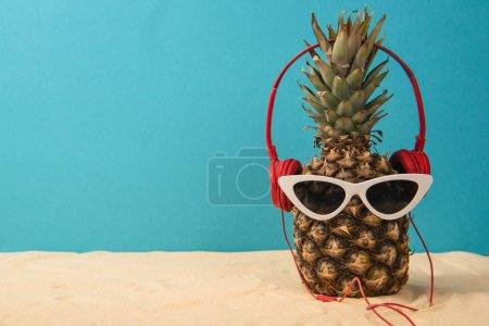 Foto de Piña con auriculares y gafas de sol en la arena en el fondo azul - Imagen libre de derechos