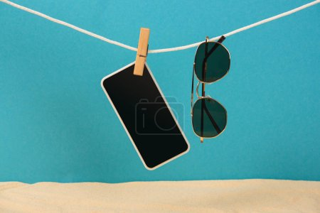 smartphone with blank screen and sunglasses hanging on rope with pin on blue background