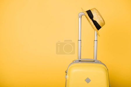 Photo for Bright yellow travel bag and straw hat on yellow background - Royalty Free Image