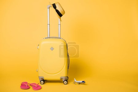 Photo for Bright yellow travel bag, straw hat, pink flip flops and plane model on yellow background - Royalty Free Image