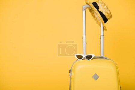 Photo pour Sac de voyage jaune vif, lunettes de soleil et chapeau de paille sur fond jaune - image libre de droit