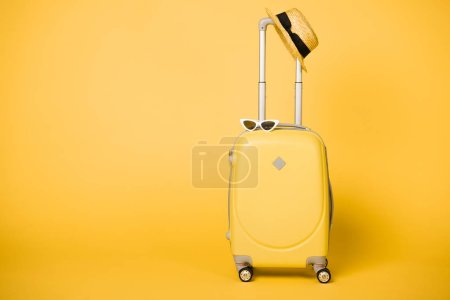 Photo for Bright yellow suitcase, sunglasses and straw hat on yellow background - Royalty Free Image