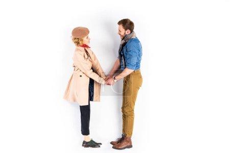 Photo pour Vue latérale du couple heureux en regardant l'autre et tenant par la main sur fond blanc - image libre de droit
