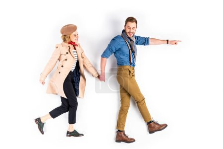 Photo for Excited couple holding hands and walking on white background - Royalty Free Image