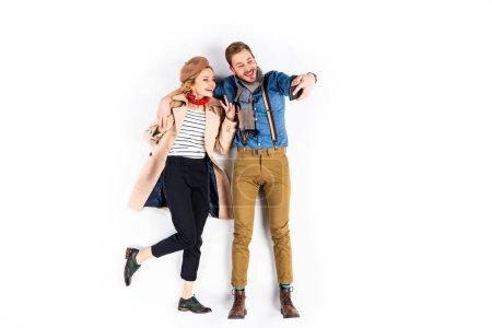 Photo pour Femme élégante, montrant le signe de la paix tout en prenant selfie avec son petit ami sur fond blanc - image libre de droit