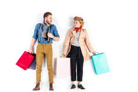 Photo for Funny couple with shopping bags looking at each other on white background - Royalty Free Image