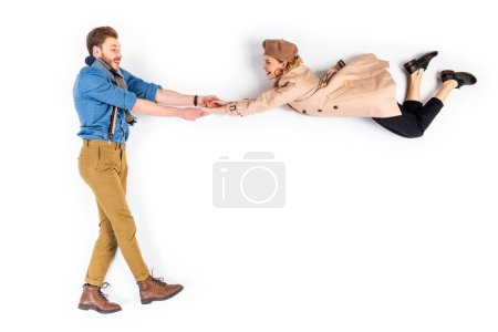 Happy couple in casual clothes holding hands on white background