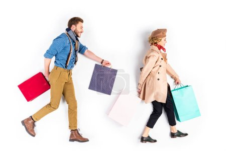 Photo for Well-dressed couple with shopping bags walking on white background - Royalty Free Image