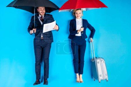 Photo pour Femme avec valise et homme avec journal debout sous des parapluies sur fond bleu - image libre de droit