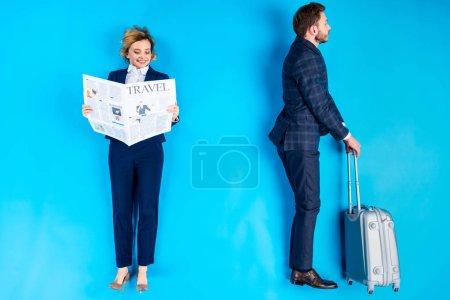 Photo pour Femme souriante lisant le journal tandis que l'homme debout avec valise sur fond bleu - image libre de droit