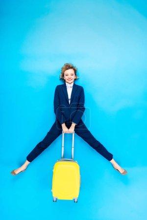 Photo pour Jeune femme insouciante tenant une valise jaune sur fond bleu - image libre de droit