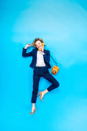 Photo for Elegant woman in suit and high-heeled shoes talking on telephone on blue background - Royalty Free Image