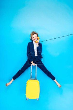 Photo pour Charmante femme en costume avec valise jaune parlant au téléphone sur fond bleu - image libre de droit