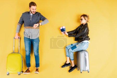 Photo pour Femme assise en valise avec des billets tandis que l'homme regardant regarder sur fond jaune - image libre de droit