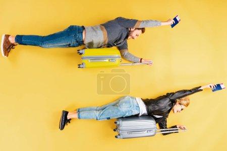 Photo pour Couple Funny couché sur les valises et détenant des billets sur fond jaune - image libre de droit