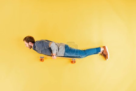 Man in casual clothes lying on longboard on yellow background
