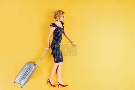 Photo for Woman in dress and high-heeled shoes holding suitcase on yellow background - Royalty Free Image