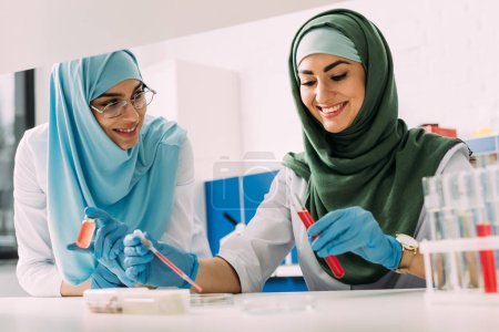 Photo for Smiling female muslim scientists in hijab with test tube and pipette during experiment in chemical lab - Royalty Free Image