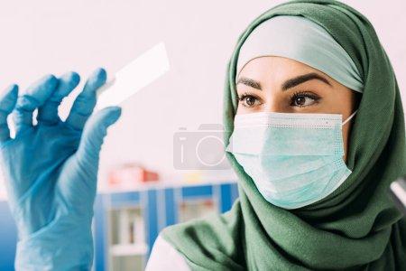Photo pour Femme scientifique musulmane en masque médical et hijab tenant échantillon de verre au cours de l'expérimentation en laboratoire - image libre de droit