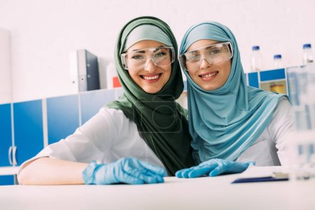 Photo pour Smiling female chimistes musulmans dans des lunettes de protection et de hijab en regardant la caméra en laboratoire - image libre de droit