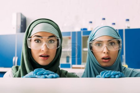 shocked female muslim chemists in protective goggles and hijab looking at camera in laboratory
