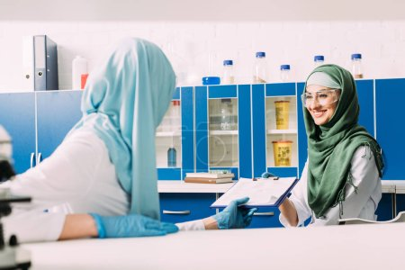 Photo for Female muslim scientists in hijab holding clipboard during experiment in chemical laboratory - Royalty Free Image